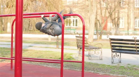 plac zabaw : Boy does sports exercises on uneven bars. Boy on a walk in city park. Happy carefree childhood Wideo