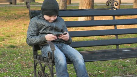 sending : Young boy with smartphone playing game near school Stock Footage