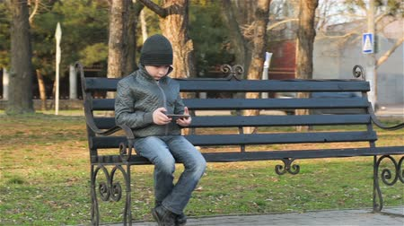 sending : Young boy sitting on bench with mobile phone. Young boy with smartphone playing game near school Stock Footage