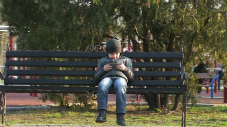 мобильный телефон : Boy with smartphone on bench use navigation. Young boy with smartphone playing game near school