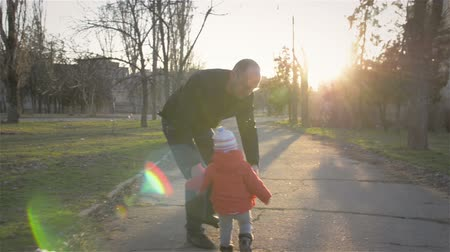 gün : Loving father throws up little girl in rays of sun. Happy family in park. Rest in city park.