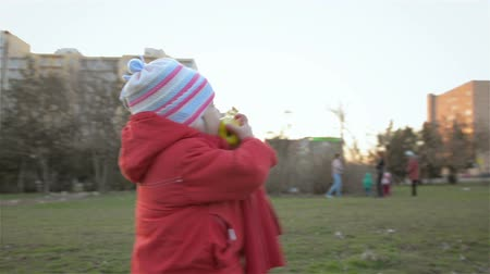 доверие : Happy little girl biting apple in park and chewing. Happy family in park. Rest in city park.