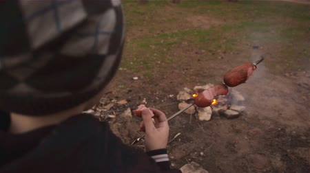 kebab : Boy eats hot sausage near campfire in forest. Family picnic in pine forest