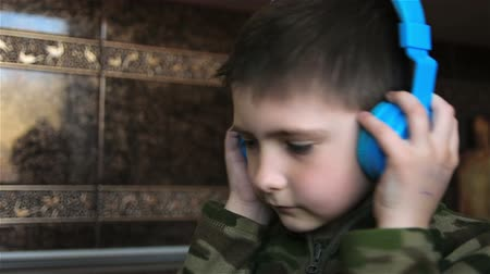 şarkı : Schoolboy with headphones turns his head to music. Little boy enjoys modern music