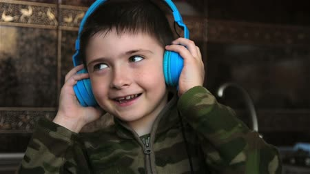 fejhallgató : Boy with headphones listening to music and smiling. Little boy enjoys modern music Stock mozgókép