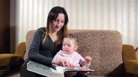 кавказский : Mother and daughter are watching family photo album. Mom shows her daughter her photo