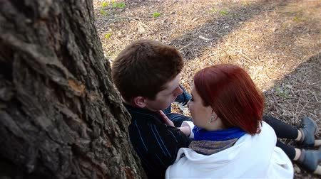 światło : Young man and red-haired girl are kissing near tree. Guy and woman are spending time on date