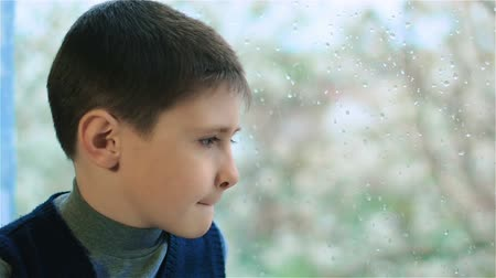 любопытство : Sad boy sits by the window with rain drops. Sad schoolboy sits by window splashed with raindrops