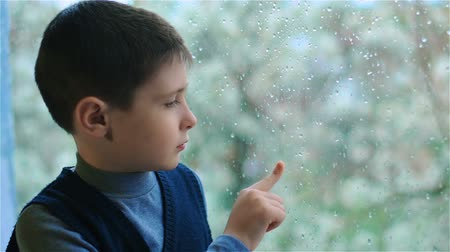 гром : Boy draws line on misted glass. Sad schoolboy sits by window splashed with raindrops
