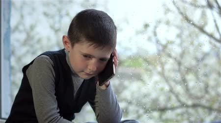 resting : Sad boy talking on phone at window in rainy weather. Sad schoolboy sits by window splashed with raindrops