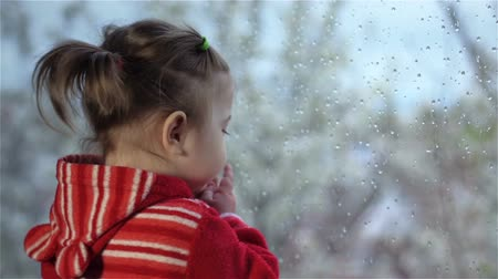 vidět : Little girl looks at rain outside window. Sad little girl sits by window splashed with raindrops