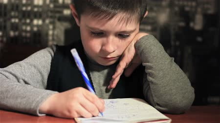 ödev : Schoolboy diligently performs his homework at table. Close up. Schoolboy writes and draws on paper late at night