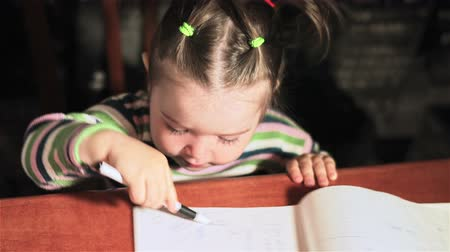 pré escolar : Little girl laughs and draws in notebooks. Little girl learns to draw by light of lamps