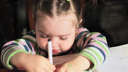 pré escolar : Little girl draws on sheet of paper and emotionally reacts to her actions. Close up. Little girl learns to draw by light of lamps Stock Footage