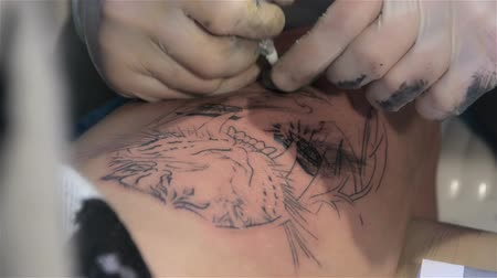 steril : Tattoo artist draws eyelashes on leg. Close up. Tattoo parlor. Patterning on skin. Body art Stok Video