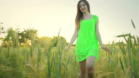 ruha : Young girl walks field outside city outside citys fuss Young woman in green summer dress in wheat field Stock mozgókép