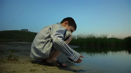 Lonely boy gathers sand from bottom of river at sunset. Boy near river on crimson sunset