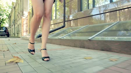 Business woman walks through autumn quarter. View on legs. Business woman walking in business district with cup of coffee Стоковые видеозаписи