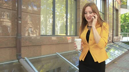 Business woman on street and talking on phone and drinking coffee from cup. Business woman walking in business district with cup of coffee