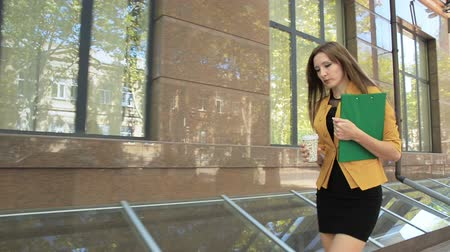Young woman walking down street with green folder and drinking coffee. Business woman walking in business district with cup of coffee