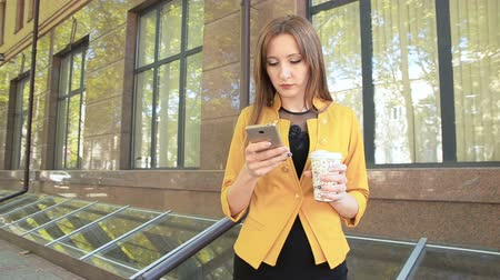 Business woman near office building writes sms on mobile phone and drinks coffee. Business woman walking in business district with cup of coffee