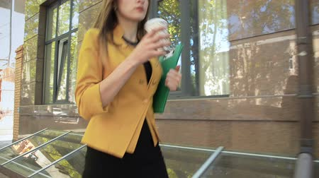 Business lady drinks street tea and walks down street. Business woman walking in business district with cup of coffee