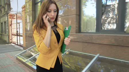 Young business woman arranges important meeting by phone. Business woman with green folder goes to business district Стоковые видеозаписи