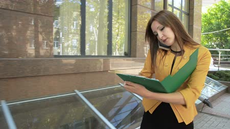 Young business woman rushes to meet with business partners and looks through important documents. Business woman with green folder goes to business district