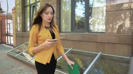 Woman is walking down street along business center and talking on her mobile phone. Business woman with green folder goes to business district Стоковые видеозаписи