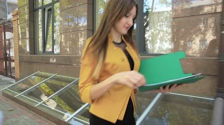 Happy business woman throws over next important documents from folder. Business woman with green folder goes to business district Стоковые видеозаписи