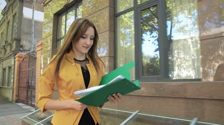 Young woman in yellow jacket throws important paper documents over her head. Business woman with green folder goes to business district Стоковые видеозаписи