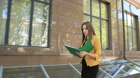 dobrador : Evil business lady throws out important documents from folder on street. Business woman with green folder goes to business district Vídeos