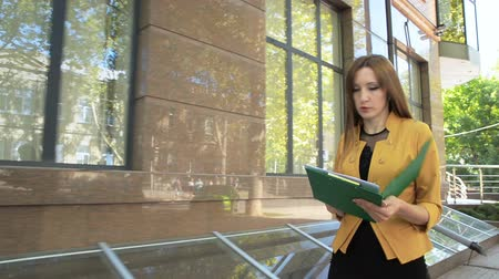 Business lady is angry and throws financial documents out of green folder. Business woman with green folder goes to business district Стоковые видеозаписи