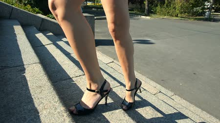 Slender woman goes up stairs. View on legs