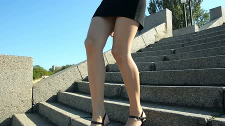 Slim young woman in sandals climbs stairs against blue sky