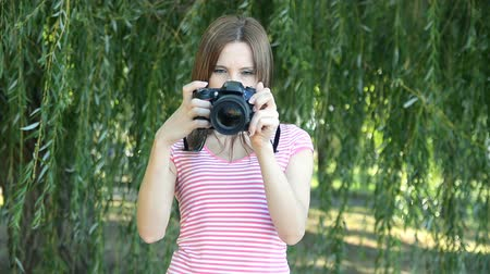 Woman amateur photographer adjusts specular professional camera Стоковые видеозаписи