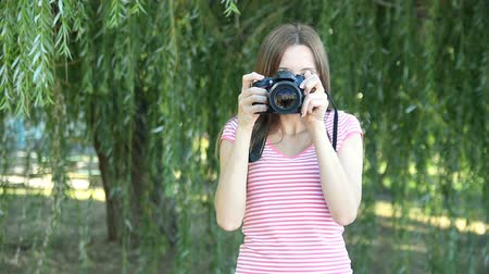 Beautiful woman tourist goes and takes photos using DSLR photo camera Стоковые видеозаписи