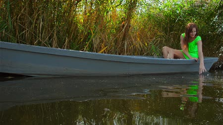 Girl sits on boat on bank of green river