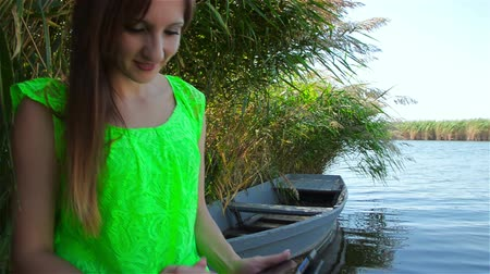 Young woman sits on boat on river bank and holds black tablet in her hands