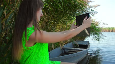 Young woman in green dress makes selfi for upgrade profiled in social networks Стоковые видеозаписи