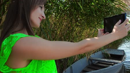 Young woman doing selfie on tablet on river bank