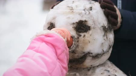 Little girl without gloves inserts carrot snowman instead nose
