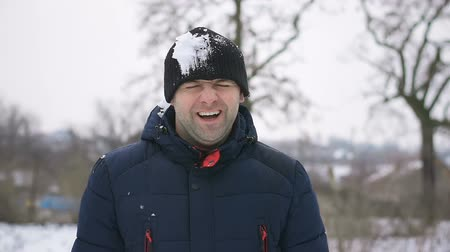 Man smiles in winter and people behind scenes throw snowballs at him and get into his head