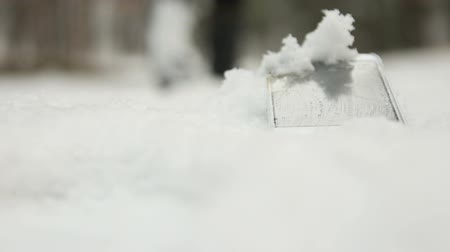 Human walks past lost phone in snow