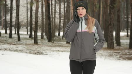 Athletic woman in sports coat talking on mobile phone in winter snowy forest Стоковые видеозаписи