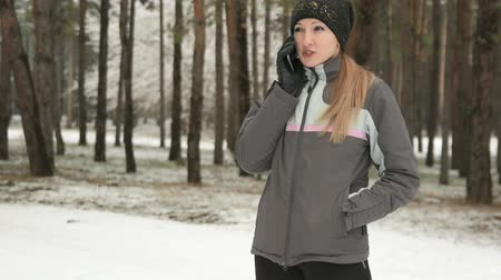 Young woman talking on mobile phone in snowy woods