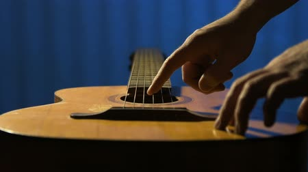 formálás : Guitarist runs his fingers over strings of acoustic guitar