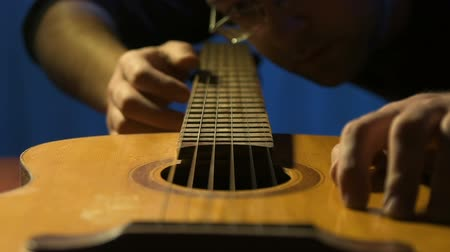 enstrüman : Craftsman checks sound of old acoustic guitars and touches of strings Stok Video