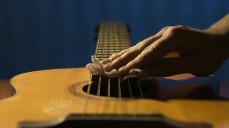 kytarista : Guitarist gently rubs strings of his acoustic guitar