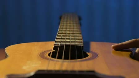 gitáros : Guitarist with nostalgia tuch old acoustic guitar and blows away dust from it